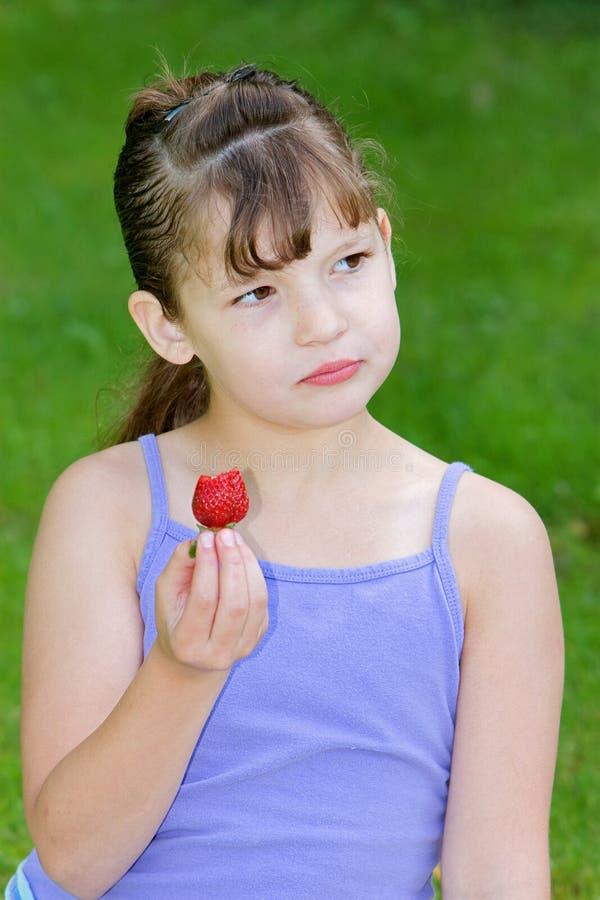 拿着严重的草莓的女孩 库存图片