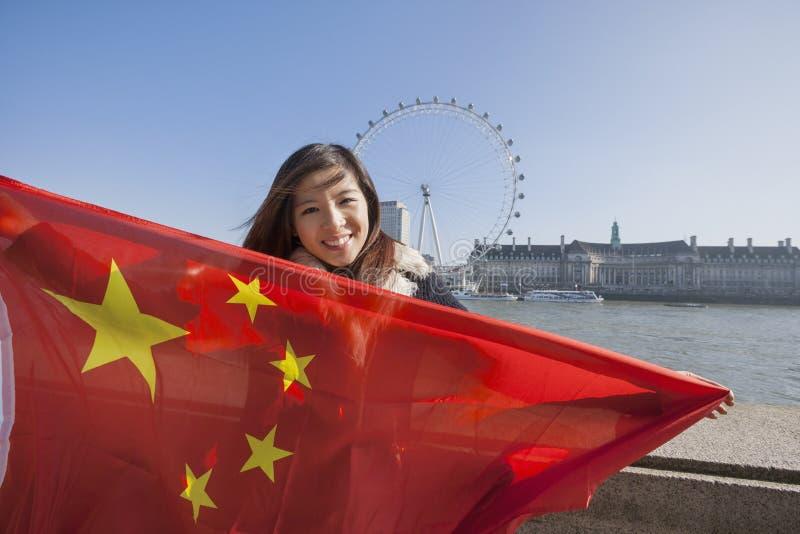 拿着中国旗子的愉快的少妇画象反对伦敦眼在伦敦,英国,英国 免版税库存照片