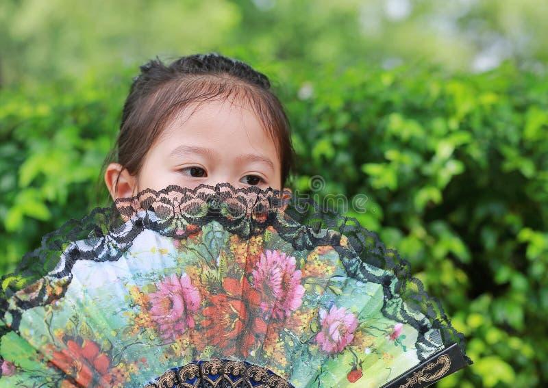 拿着中国风格爱好者的小亚裔儿童女孩画象在夏天庭院掩藏她的面孔 图库摄影