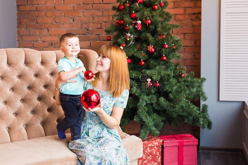 拿着中看不中用的物品的愉快的母亲和孩子画象反对与圣诞树的国内欢乐背景 免版税库存图片