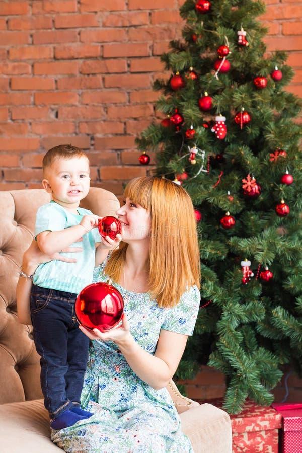 拿着中看不中用的物品的愉快的母亲和笑的婴孩画象反对与圣诞树的国内欢乐内部 图库摄影