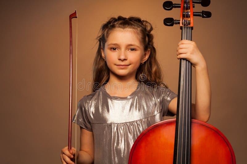 拿着串的微笑的女孩演奏大提琴 免版税图库摄影