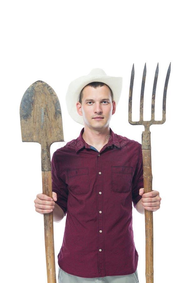 拿着为处理的帽子的农夫土壤的一个工具 库存图片