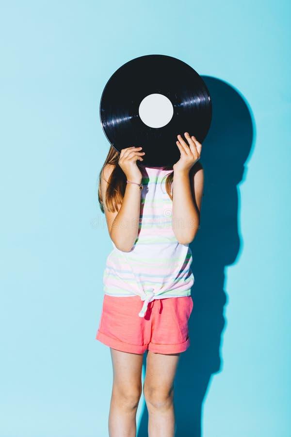 拿着乙烯基圆盘的小女孩反对她的头 库存图片