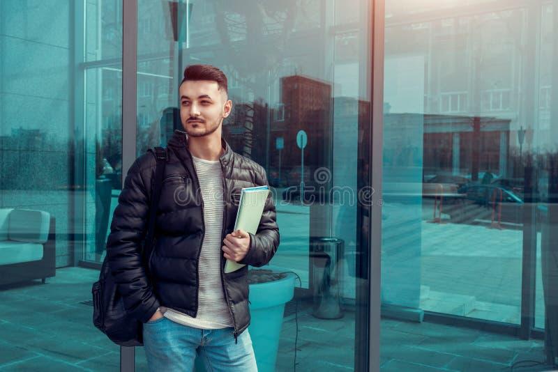 拿着习字簿的阿拉伯学生由现代大厦外面 年轻人等待的groupmates 库存照片