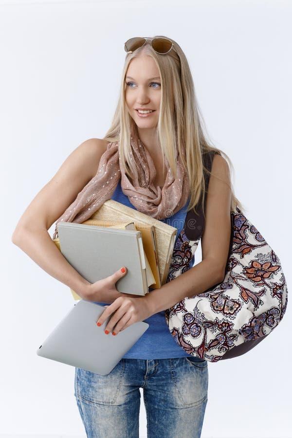 拿着书和片剂的学生 免版税库存照片