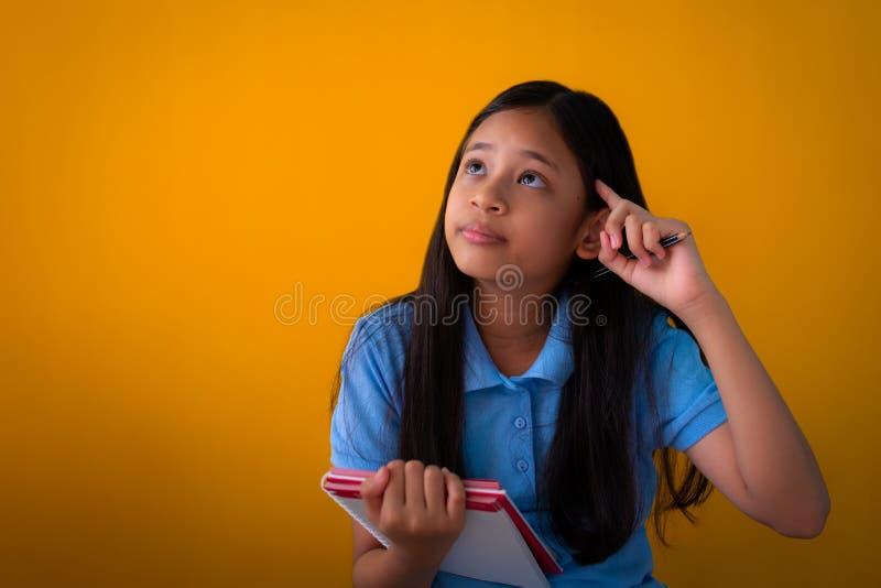 拿着书和认为橙色背景的亚裔逗人喜爱的女孩画象  免版税库存图片