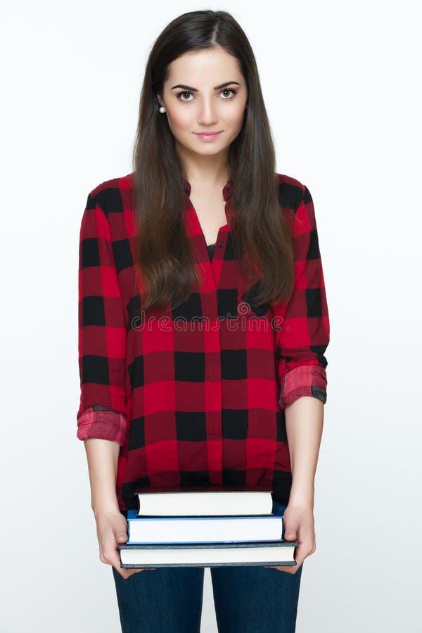 拿着书的可爱的快乐的年轻女学生,隔绝在白色背景 免版税库存照片