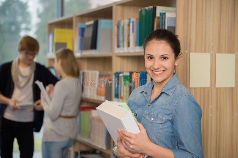 拿着书的学生在大学图书馆里 免版税库存照片