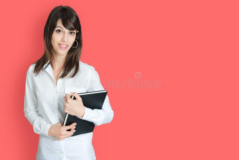 拿着书的年轻女人 免版税库存照片