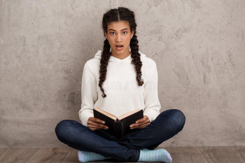 拿着书的惊奇的美丽的非洲女孩,坐在米黄背景 免版税库存图片