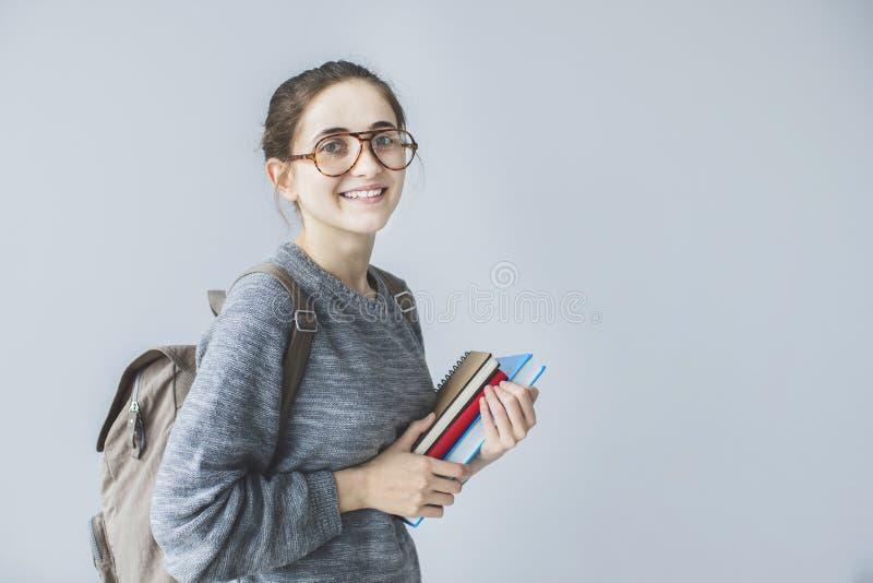 拿着书的愉快的年轻女学生运载的背包看照相机 免版税图库摄影