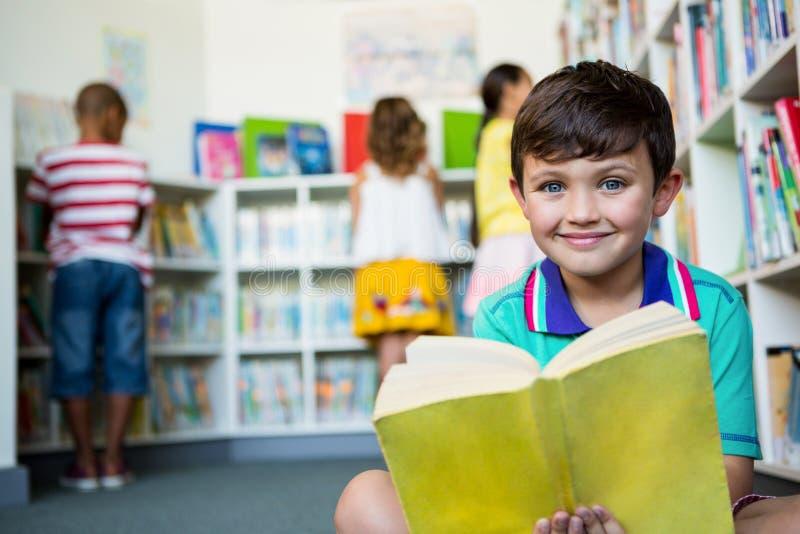 拿着书的男孩画象在学校图书馆 库存照片