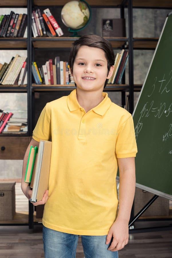 拿着书的男小学生,当站立近的黑板时 库存照片