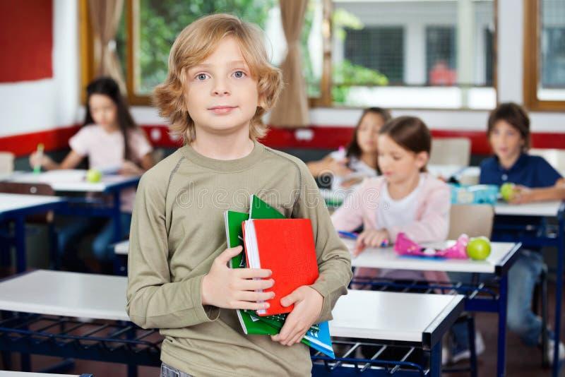 拿着书的男小学生 免版税库存照片