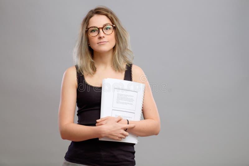 戴拿着书的眼镜的学生女孩 库存照片