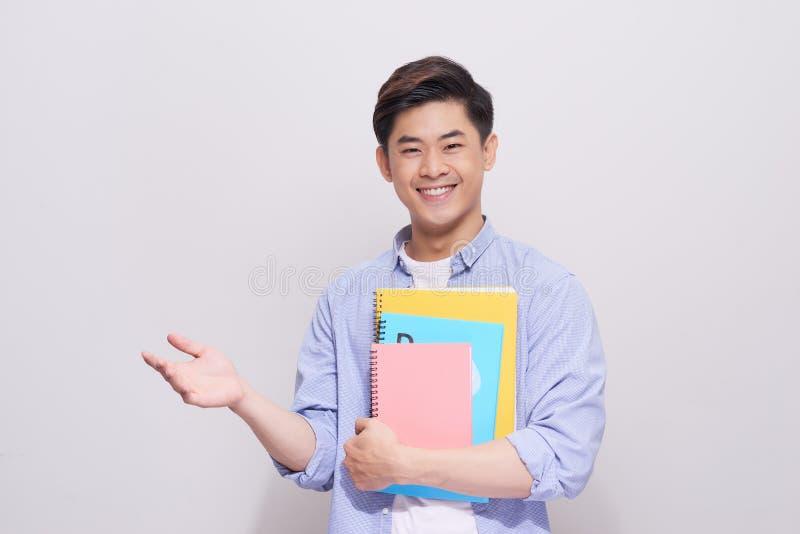 拿着书的确信的亚裔英俊的学生打手势手 免版税库存图片