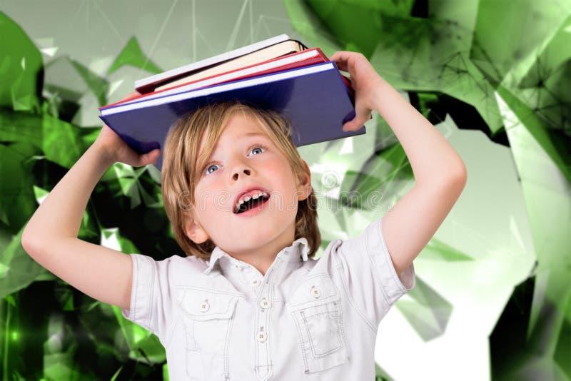 拿着书的逗人喜爱的学生的综合图象 免版税图库摄影