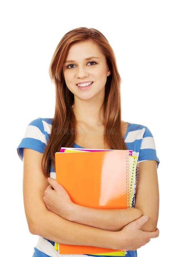 拿着书的年轻人微笑的少年妇女 库存图片