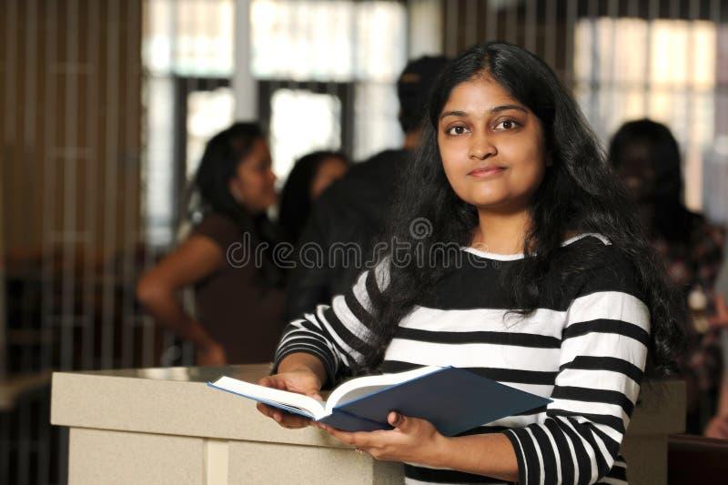 拿着书的年轻印地安学生 库存照片