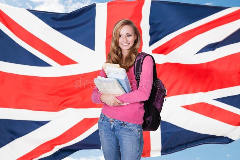 拿着书的年轻女学生 免版税库存图片