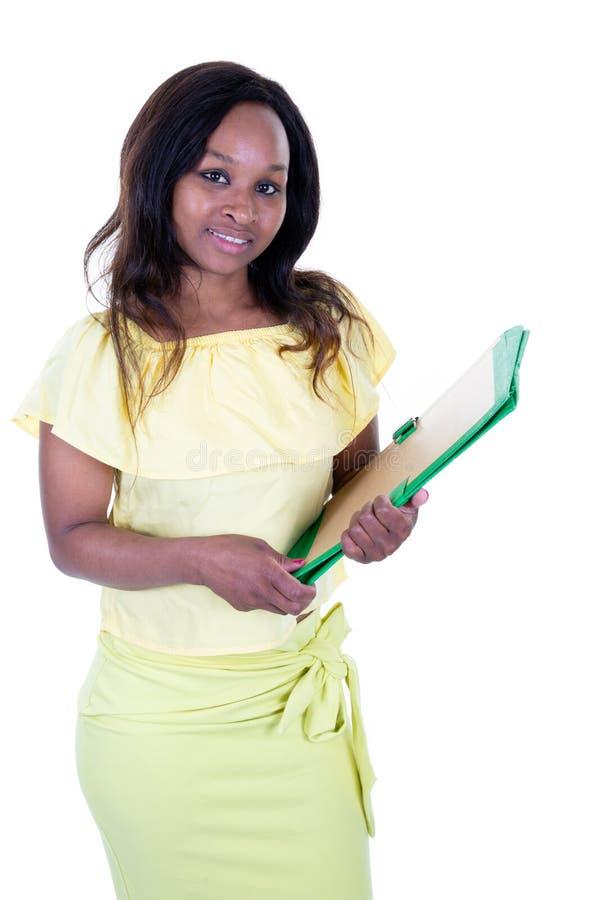 拿着书纸的非裔美国人的学生女孩女商人 免版税库存照片
