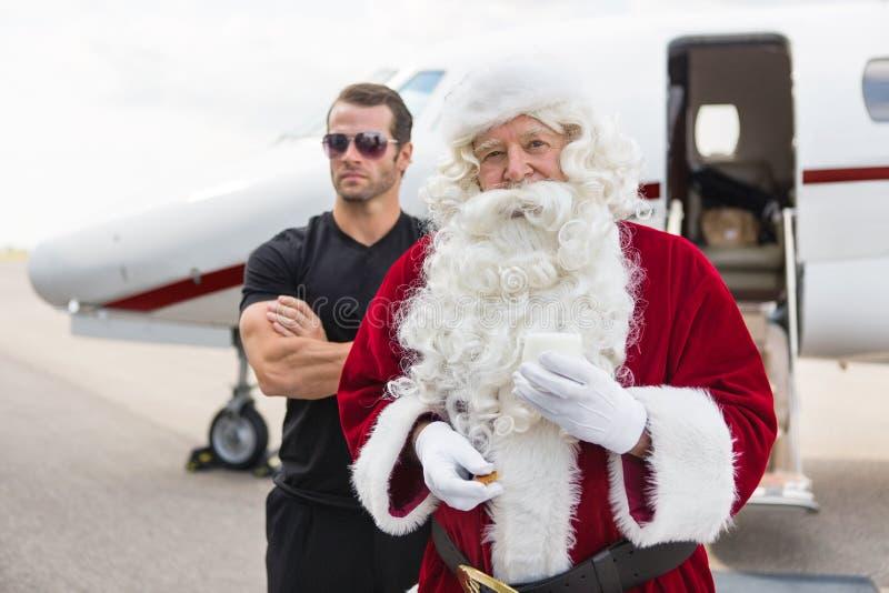 拿着乳白玻璃的圣诞老人由保镖反对 库存照片