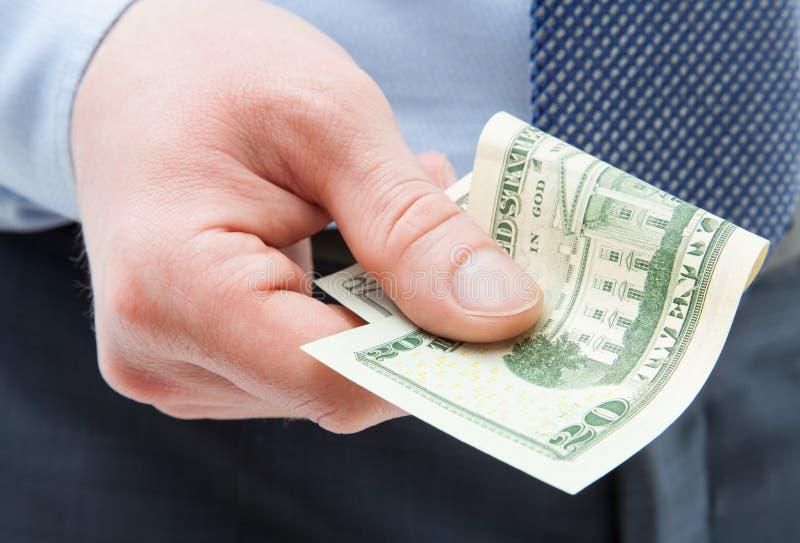 拿着二十美元的无法认出的商人 免版税库存照片
