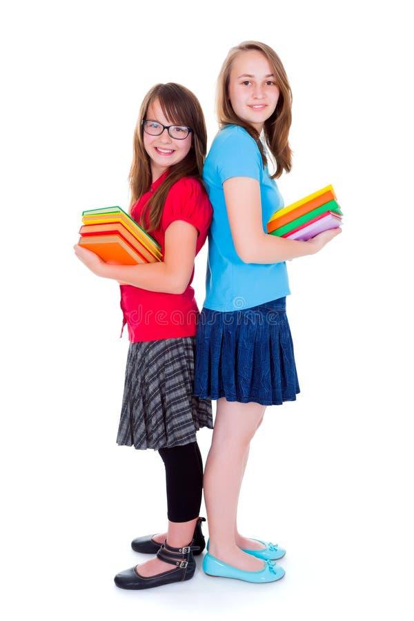 拿着五颜六色的书的愉快的女小学生 免版税库存图片