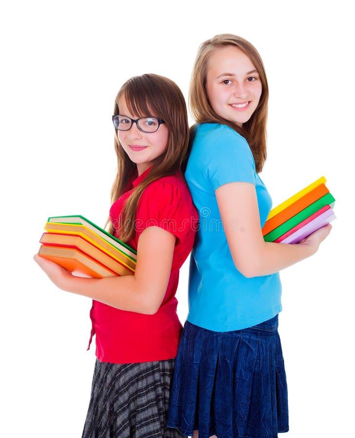 拿着五颜六色的书的愉快的女小学生 库存照片