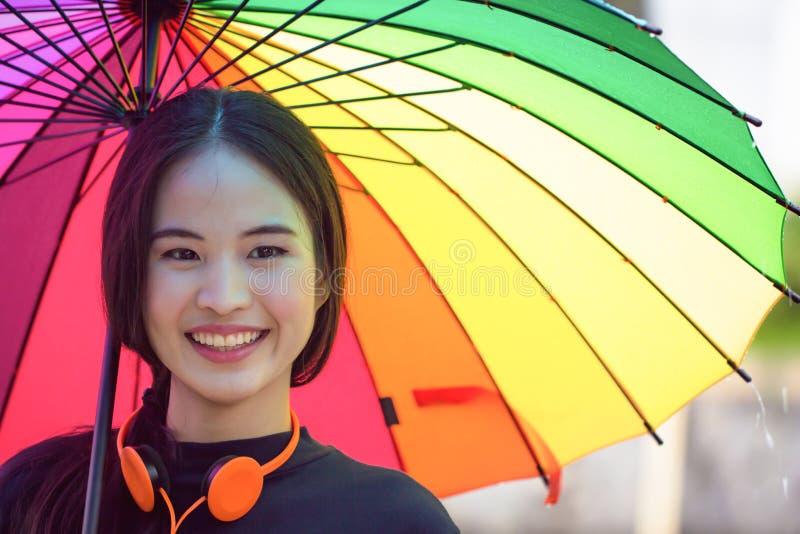 拿着五颜六色的伞的年轻亚裔妇女,当下雨时 愉快 库存照片