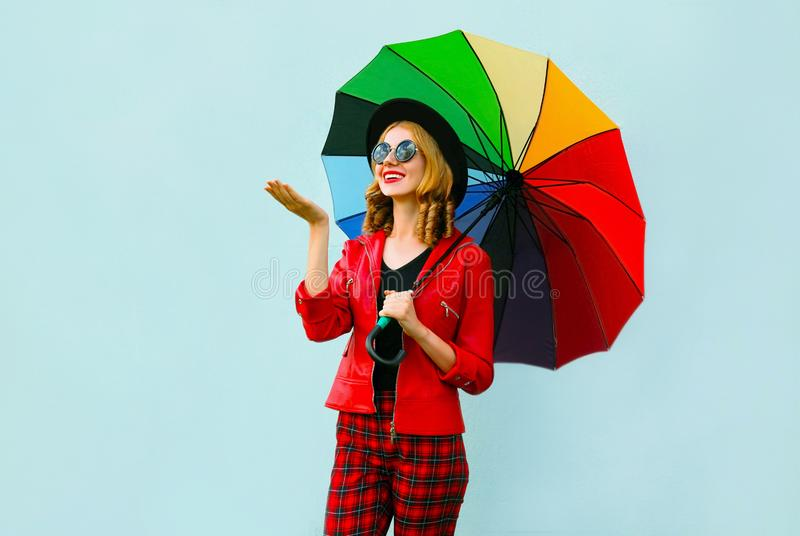 拿着五颜六色的伞的愉快的微笑的年轻女人,检查与被伸出的手雨,佩带的红色夹克,在蓝色的黑帽会议 免版税库存照片