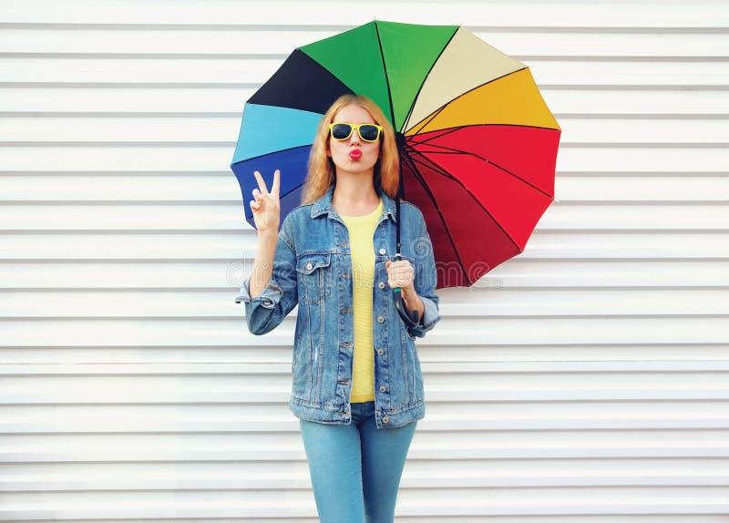拿着五颜六色的伞的时髦的凉快的女孩吹送在白色墙壁背景的红色嘴唇甜空气亲吻 免版税库存图片