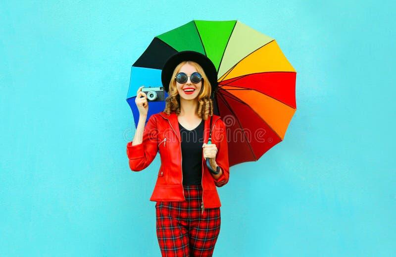 拿着五颜六色的伞,减速火箭的照相机的愉快的微笑的妇女拍在红色夹克,在蓝色墙壁上的黑帽会议的照片 免版税库存图片