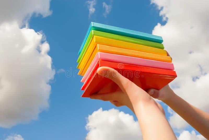 拿着五颜六色的坚硬盖子书的手 图库摄影