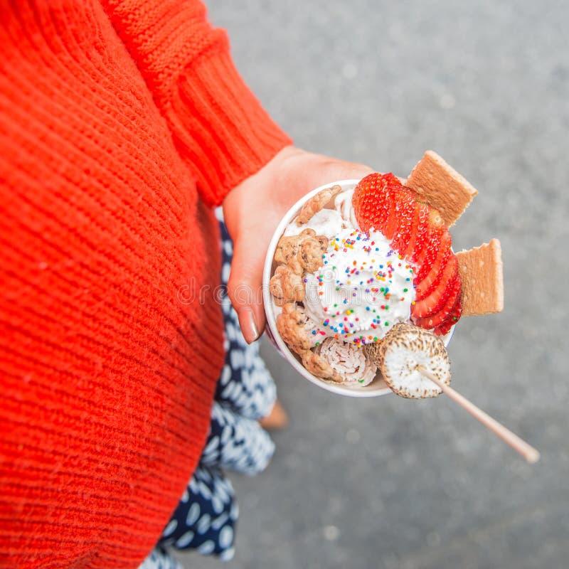 拿着五颜六色的手工制造冰淇凌杯子用草莓和蛋白软糖的女孩户外 免版税库存照片
