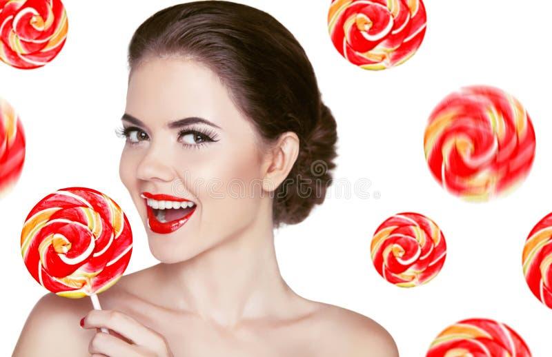 拿着五颜六色的棒棒糖的愉快的微笑的女孩被隔绝在白色b 库存图片