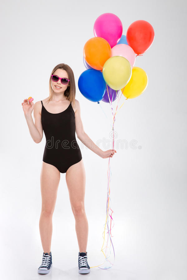 拿着五颜六色的气球和小蛋白杏仁饼干的正面俏丽的女孩 免版税图库摄影