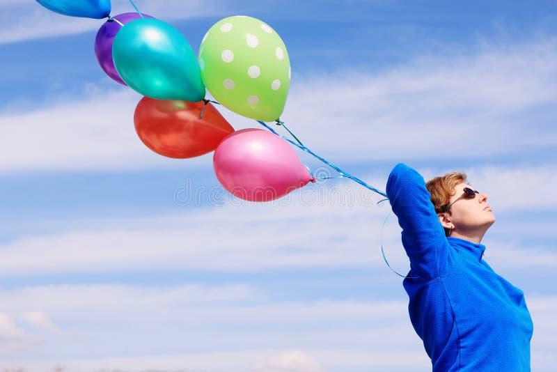 拿着五颜六色的气球的妇女 免版税库存图片