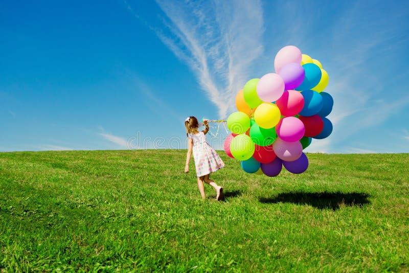 拿着五颜六色的气球的小女孩。使用在绿色的孩子 库存照片