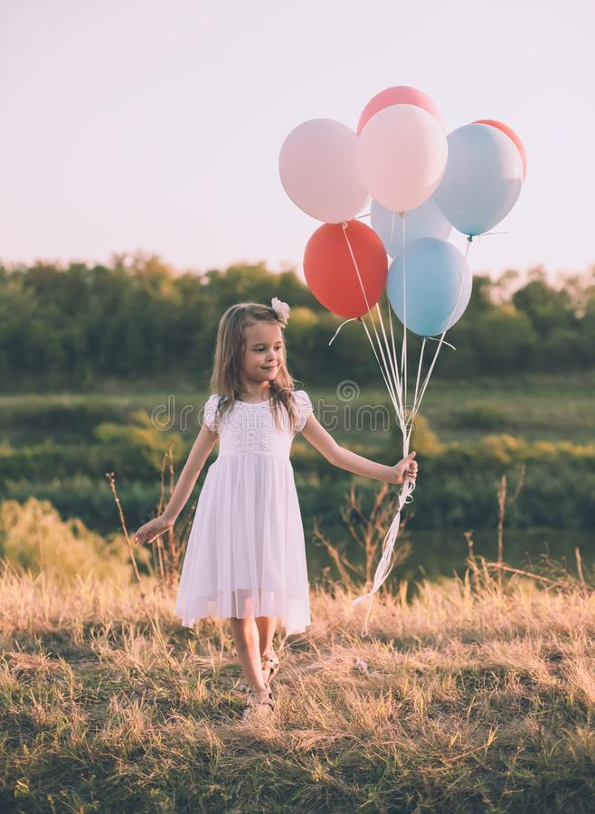 拿着五颜六色的气球的小女孩在草甸 免版税库存照片