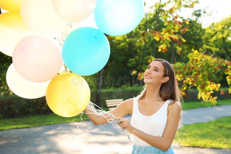 拿着五颜六色的气球的美丽的十几岁的女孩 免版税库存图片