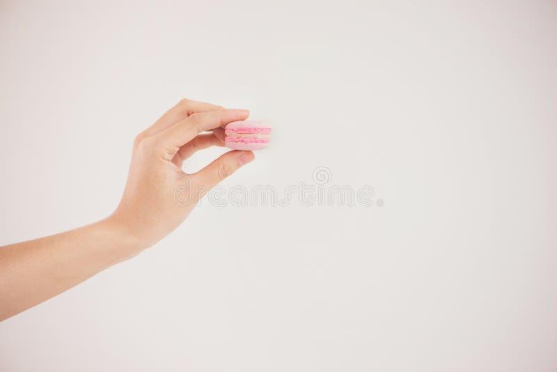 拿着五颜六色的淡色蛋糕macarons或蛋白杏仁饼干的手 免版税库存图片