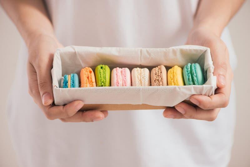 拿着五颜六色的淡色蛋糕macarons或蛋白杏仁饼干的手 库存图片