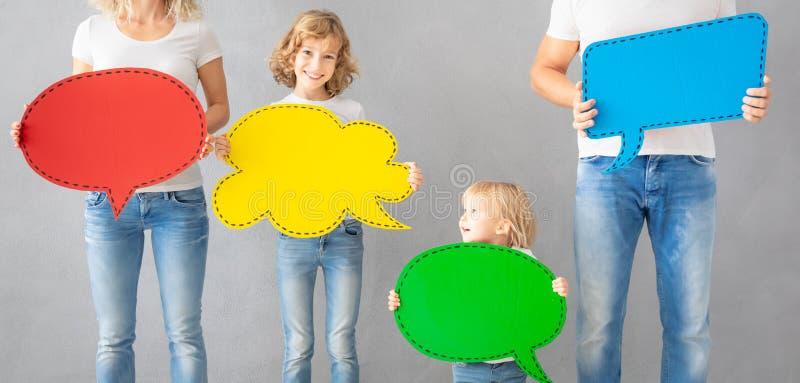 拿着五颜六色的纸讲话泡影空白的幸福家庭 免版税库存图片