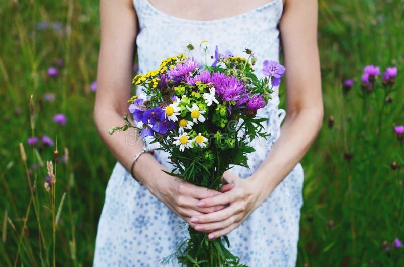 拿着五颜六色的花的花束乡村模式的礼服的妇女 免版税库存图片