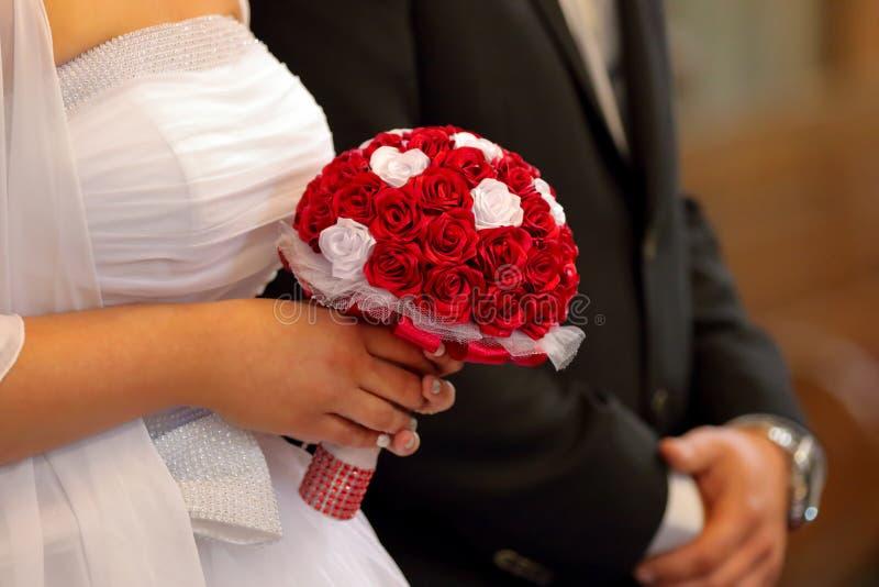 拿着五颜六色的花花束用她的在婚礼的手的新娘 库存照片