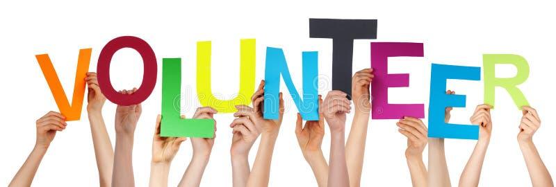 拿着五颜六色的词志愿者的人手 库存照片