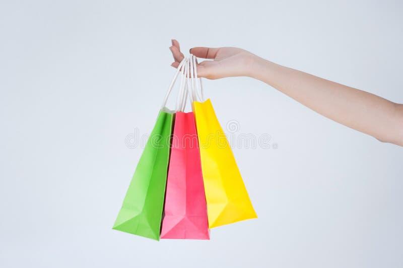 拿着五颜六色的购物带来有白色背景的愉快的妇女 图库摄影