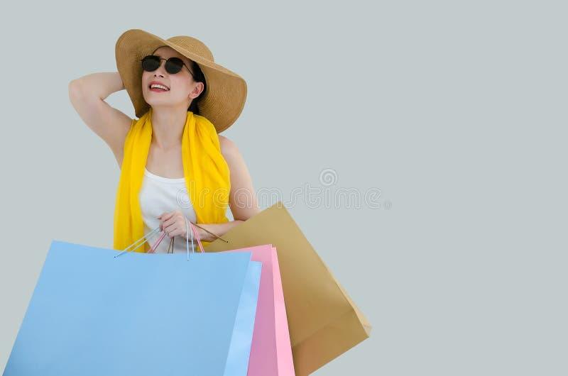 拿着五颜六色的购物带来的一名愉快的亚裔俏丽的妇女的画象被隔绝在白色背景 妇女爱购物的概念 库存图片